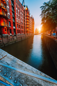 Touristic spot old red brick illuminated buildings, canal and square in golden sunset light. Speicherstadt Hamburg. Warehause District at dawn