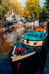 Traditional cruising tour boat moored tied up in one of the famous Amsterdam canals on the beautiful, sunny autumn day