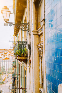 Traditional facade front of portuguese buildings with balconys and lamps. Old charming street in Lisbon , Portugal