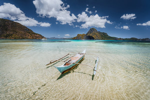 Traditional filippino fishermen banca boat in blue tropical lagoon at El Nido bay with Cadlao Island on Background. Palawan Island, Philippines