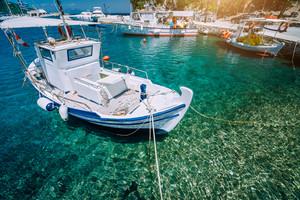 Traditional fishing boat in crystal clear Mediterranean sea. Blue bay on the Greek island