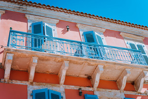 Traditional greek house facade with blue windows, shutters and balconies, Greece