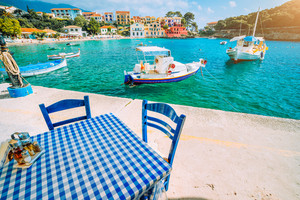 Traditional Greek restaurant with blue and white table and chairs at the sea coast of Assos village. Azure water, sunshine, summer feeling summer vacation