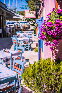 Traditional greek vivid colored tavern on the narrow Mediterranean street on hot summer day