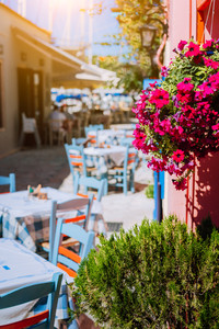 Traditional Greek vivid colored tavern with purple flowers on the narrow Mediterranean street on hot summer day