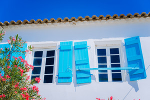 Traditional greek white house with blue window shutter and flowers in Fiskardo, Kefalonia island, Greece