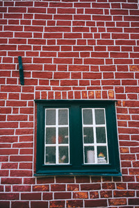 Traditional medieval German brick house in Luneburg, Germany. Fragment of the red brick facade with window frames