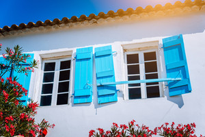 Traditional white greek white with blue window shutter in Mediterraneanstyle and rosa flowers. Fiskardo, Kefalonia island, Greece