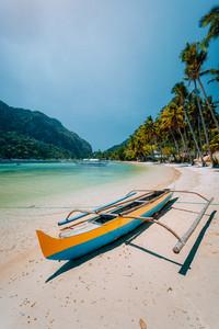 Traditional wooden banca boat on beautiful Las Cabanas beach. Summer vacations, Island hopping, El Nido, magic of Philippines