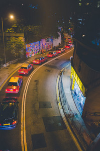 Traffic jam in Hong Kong at night. Taxy cars standing in queue. Curve remote street