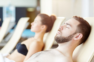 Tranquil man with his eyes closed enjoying vacation at spa resort