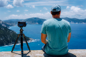 Travel Europe summer holiday in Greece. Happy man photographer enjoying cloudscape, coastline and Mediterranean sea visiting Kefalonia Island on cruise vacation. Camera on tripod capture timelapse