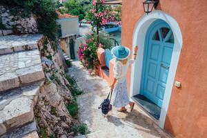 Travel tourist blonde woman with sun hat walking through narrow streets of an old greek town to the beach. Vacation summertime perfekt summer day joyful holidays fun. Greece, Europe