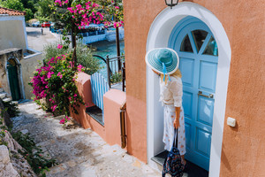 Travel tourist woman on vacation in Greece. Person with blue sunhat in front of traditional Mediterranean house. Colored houses, cozy picturesque alley, tranquil village. Europe summer destination