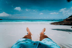 Travel vacation background male legs with swim short on paradise white sand tropical beach in front of turquoise sea. Exotic holidays