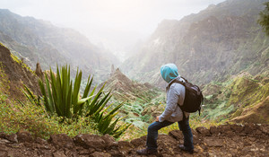 Traveler with backpack looking over the rural landscape with mountain peaks and ravine in dust air on the path from Xo-Xo Valley. Santo Antao Island, Cape Verde