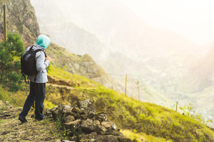 Traveler with backpack staying on the edge of path leading through rural landscape with mountains, on the way of the Paul Valley. Santo Antao Island, Cape Verde