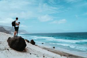 Traveler with camera staying on the black volcanic boulder and admiring unusual barren landscape of Baia Das Gatas beach. North of Calhau, Sao Vicente Island Cape Verde