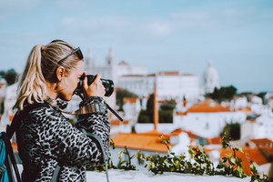 Traveler woman make a picture of Lisbon cityscape. The National Pantheon and the towels of Vicente de Fora come into view. Roofs of Lisbon