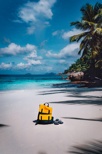 Traveler yellow backpack and flip flops on the sandy tropical beach on summer holidays trip, travel background with copy space