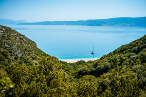 Trekking path to White sand beach beach that appearing in the distance surrounded by mediterranean vegetation. Amazing seascape Greece Ionian islands. Summer adventure vacation