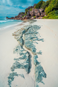 Tropical beach at Grand Anse, La Digue island, Seychelles. Beautifully shaped granite boulders, white sand and blue ocean