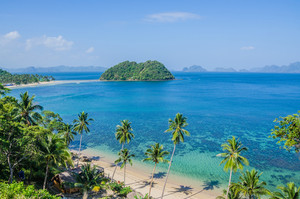Tropical Beach with Palm trees. Many Islands in ocean in Background, El Nido, Palawan, Philippines