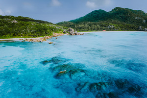 Tropical coastline of La Digue island with granite boulders and paradise beaches, view from the sea, Seychelles