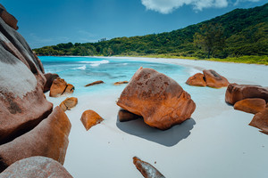 Tropical lagoon with granite boulders in the turquoise water and a pristine white sand at Anse Cocos, La Digue island, Seychelles
