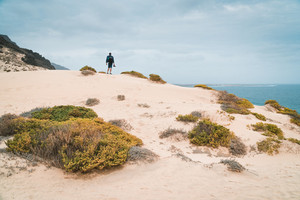 Ttraveler and photographer on the top of snow-white dune landscape on the Atlantic coastline. Sao Vicente, Cape verde