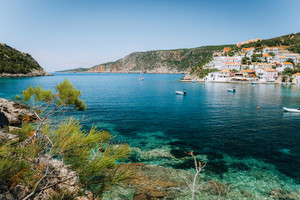 Turquoise transparent lagoon surrounded by green pine trees. Assos village, Kefalonia Greece. Blue deep pattern on Mediterranean sea bottom
