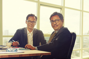 two asian business man toothy smiling face in working office