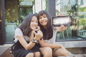 two asian teenager happiness face show screen display of smart phone in hand