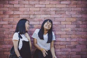 two asian teenager laughing with happiness emotion standing against red brick wall