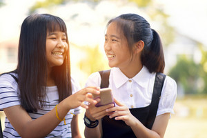 two asian teenager laughing with happiness face reading message in smart phone screen