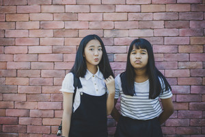 two asian teenager standing in front of red brick wall with surprising face