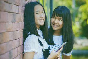 two asian teenager toothy smiling face with happiness emotion holdhing smartphone in hand