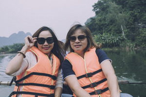 two asian woman tourist wearing lifejacket sailing boat in ninh binh canal most popular traveling destination in vietnam
