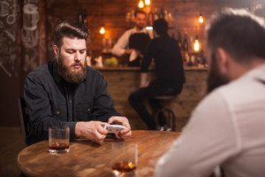 Two bearded hipsters playing a card game in a vintage pub. A bartender with a client is in the background