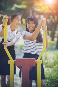 two cheerful asian teenager toothy smiling face in public playground