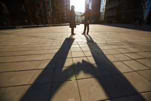 Two cheerful business partners shaking hands while standing at modern office buildings, last beams of setting sun illuminating them, lens flare