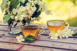 Two cups of green tea with jasmine flowers on grunge wooden table in the garden