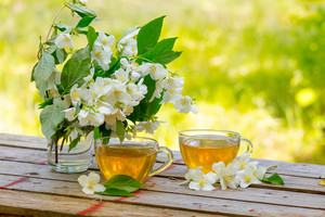 Two cups of green tea with jasmine flowers on grunge wooden table outdoors