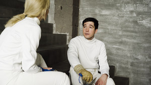 Two fencers man and woman sharing experience during break of fencing match indoors