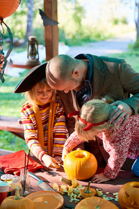 Two girls helping their father to prepare Halloween jack-o-lanterns