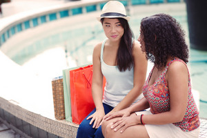 Two girls sitting together with shopping bags