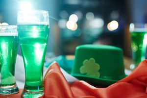 Two glasses of irish beer on background of green hat
