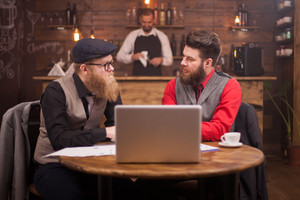 Two handsome businessmen looking at each other while talking about finances in a vintage pub. Stylish beard. Coffee cup. Laptop