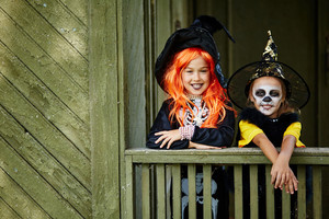 Two happy Halloween girls standing by old house
