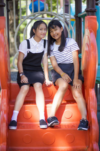 two lovely asian teeenager relaxing in children play ground